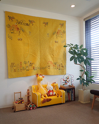 壁一面に広がるキルト、木のおもちゃと絵本が並ぶチャイルドスペース